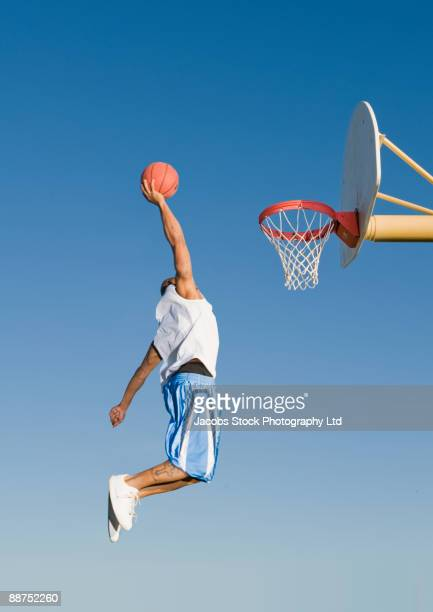 man playing basketball outdoors - shooting baskets stock pictures, royalty-free photos & images