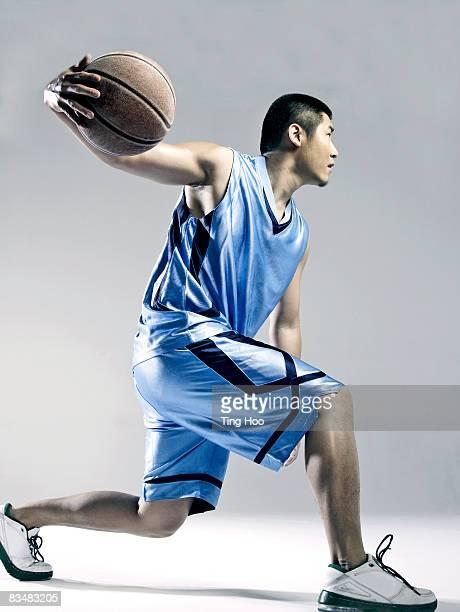 man playing バスケットボール、サイドの眺め - ドリブル ストックフォトと画像