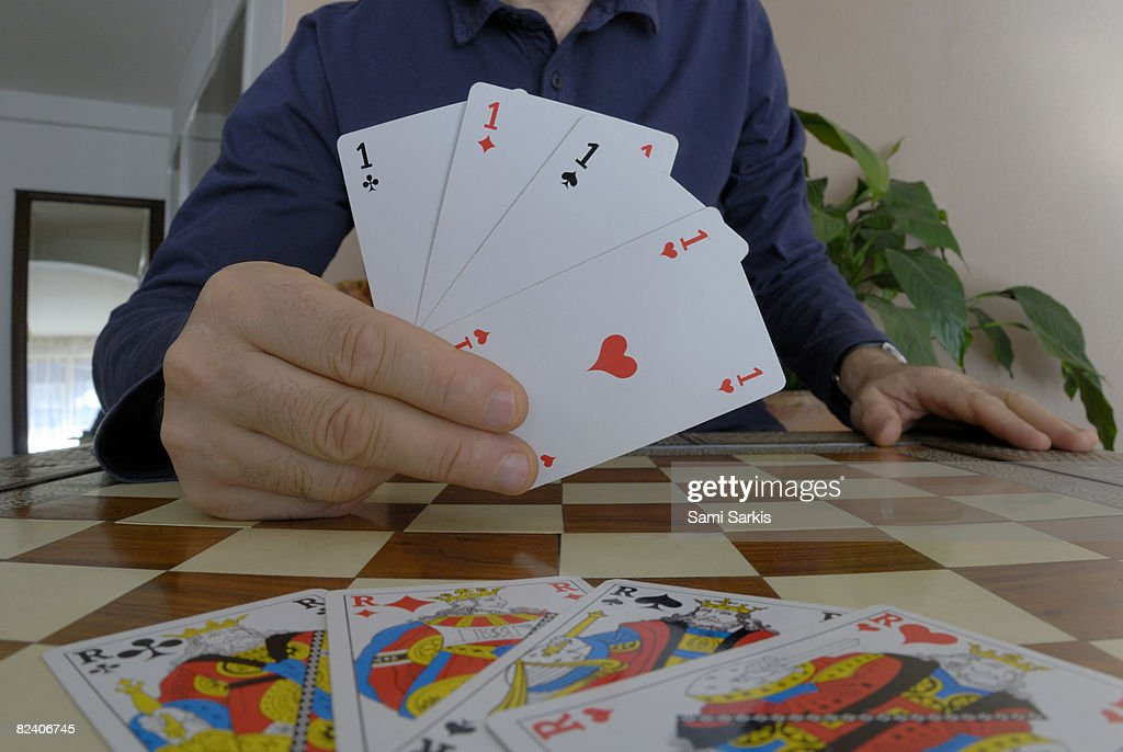 Man playing cards, showing four aces : Stock Photo