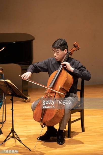 man playing cello at classical music concert - classical concert stock pictures, royalty-free photos & images