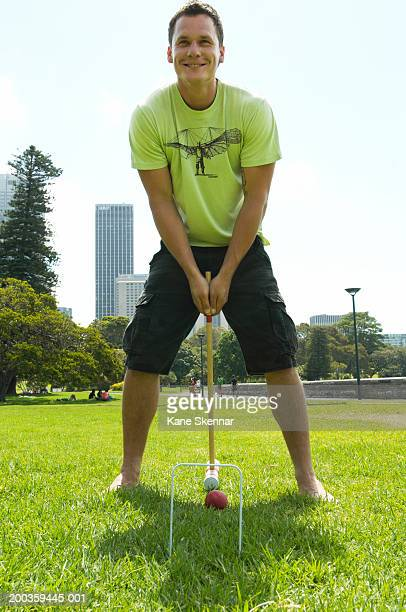 Man playing croquet in park