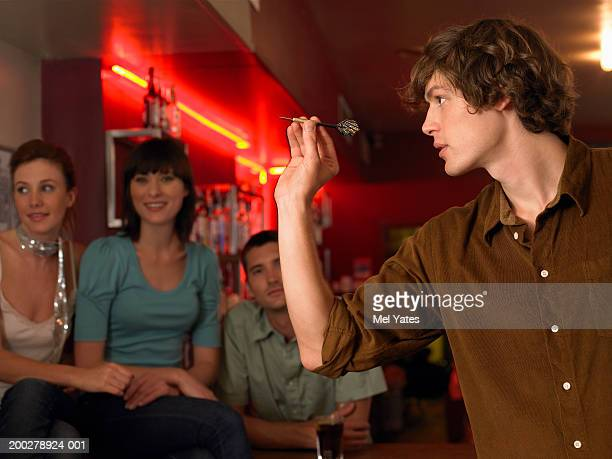 Man playing darts, friends watching at bar (focus on man)