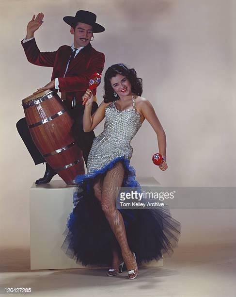 Homme jouant du tambour, femme tenant maraca