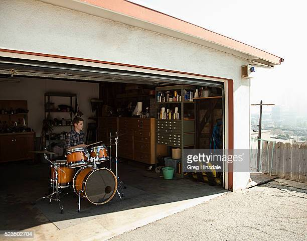 man playing drums in garage - drum kit stock pictures, royalty-free photos & images