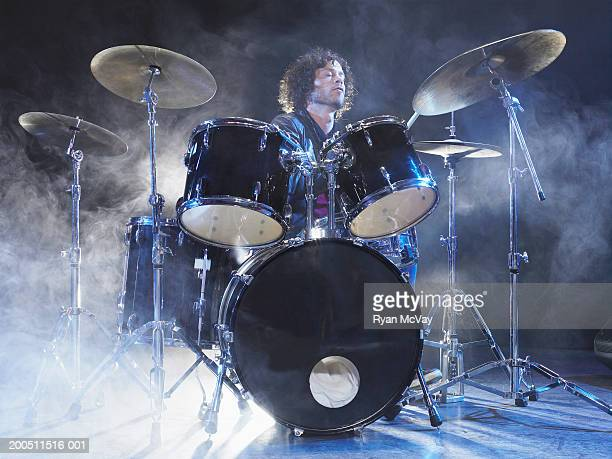 man playing drums on stage surrounded by dry ice - drummer stock photos and pictures