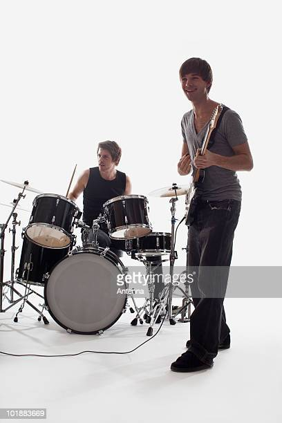 A man playing electric guitar and a man on drums performing, studio shot, white background, back lit