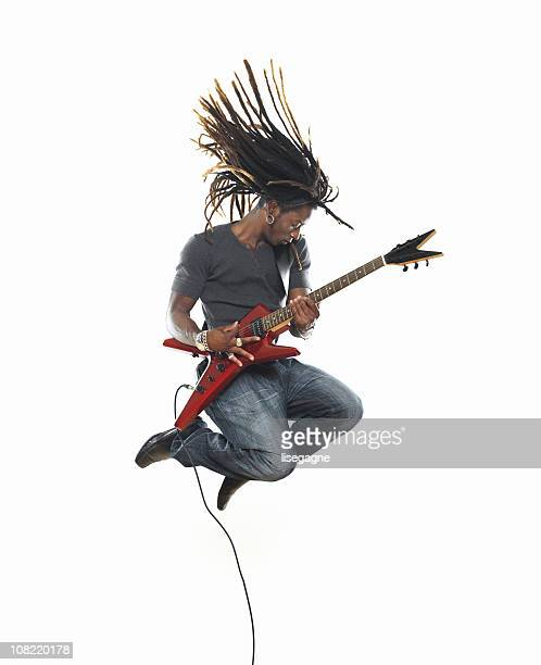 man playing electric guitar and jumping - electric guitar stock pictures, royalty-free photos & images