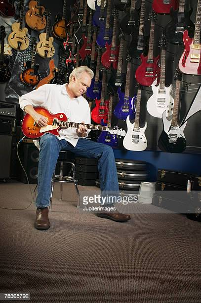 Man playing electric guitar in music store