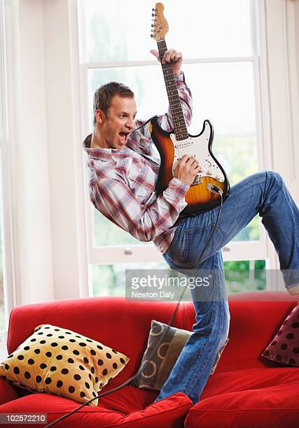 Man playing electric guitar on sofa