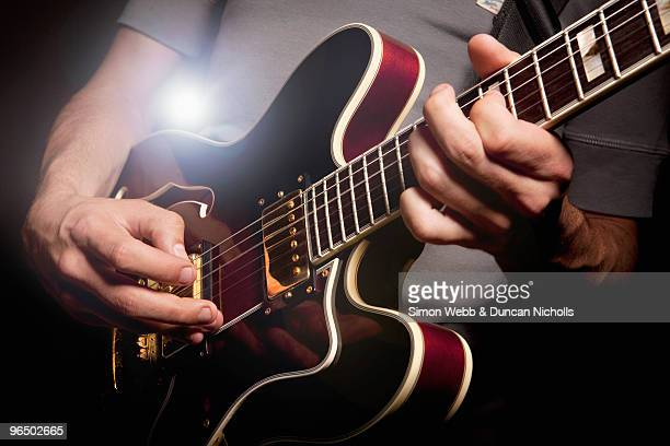 man playing electric guitar - electric guitar stock pictures, royalty-free photos & images