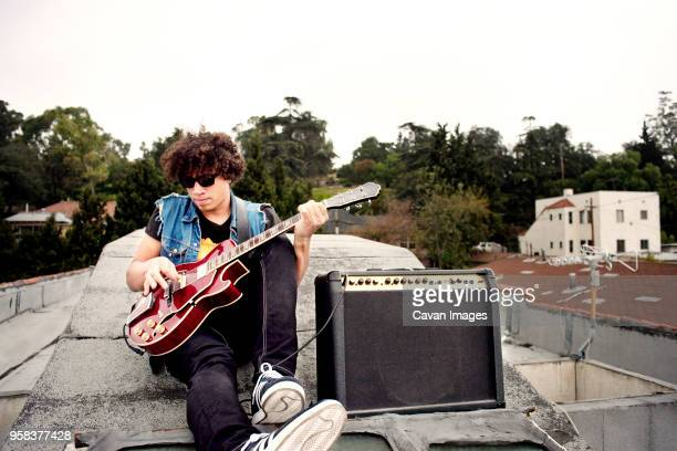 man playing electric guitar while sitting on building against sky - verstärker stock-fotos und bilder