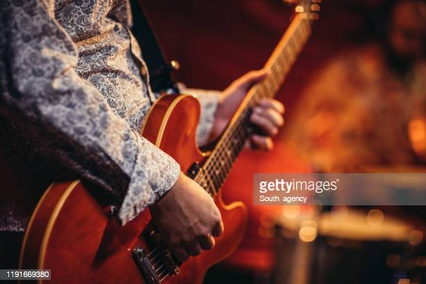 man playing electric guitarist on stage - modern rock stock pictures, royalty-free photos & images