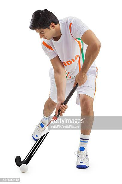 Man playing field hockey isolated over white background