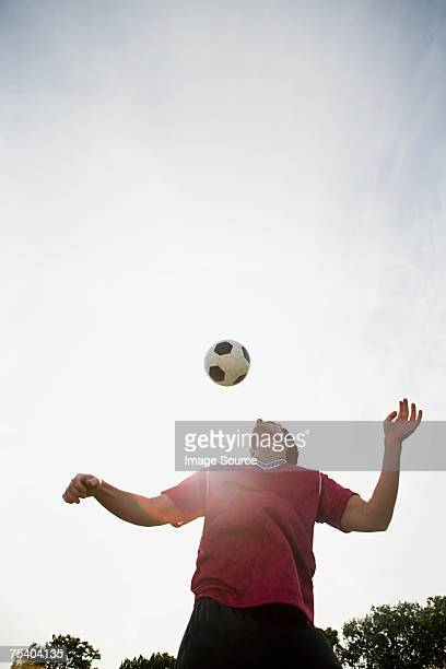 Man playing football in sunlight