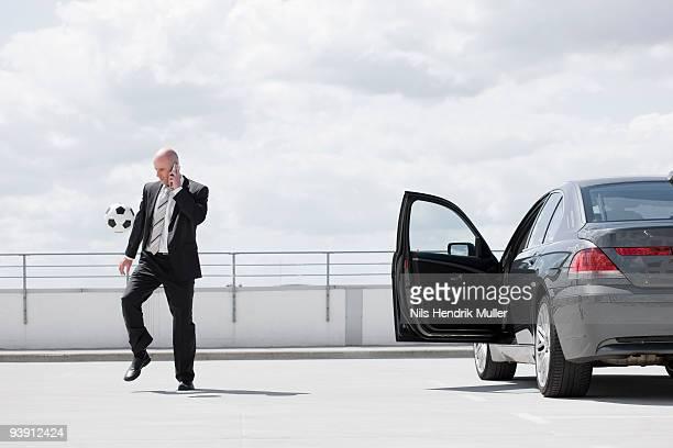 man playing football near car