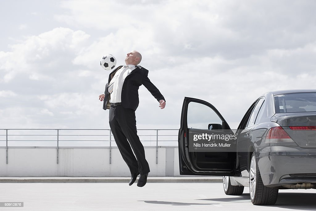 man playing football near car : Stock Photo