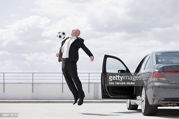 man playing football near car