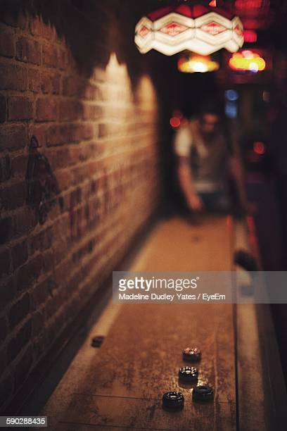 Man Playing Game By Brick Wall In Bar