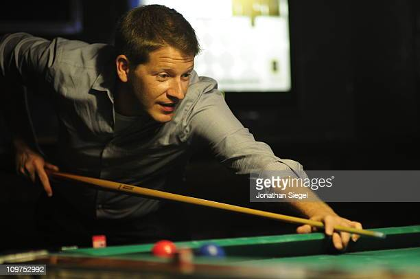 Man playing game of billiards in pool parlor