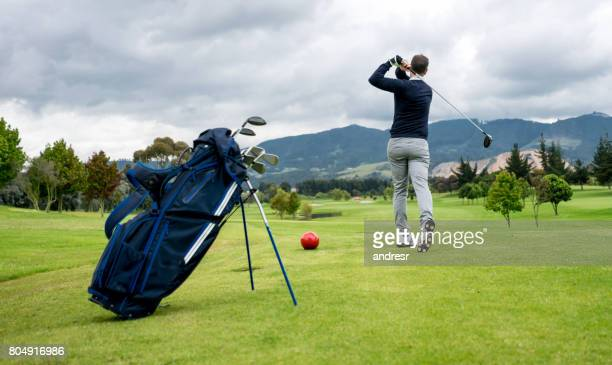 Man playing golf and practicing his swing on the tee box
