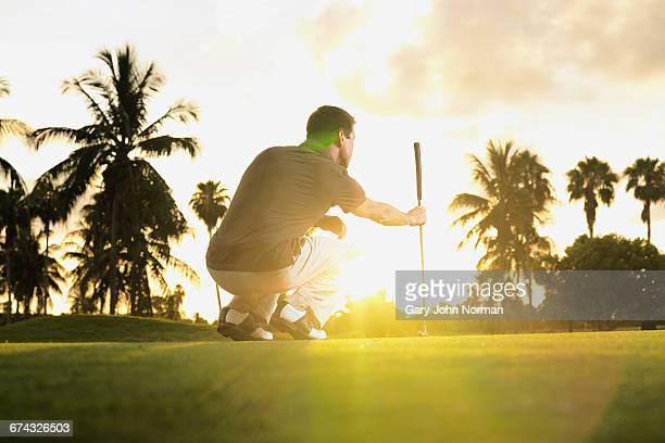Man playing golf in early morning light