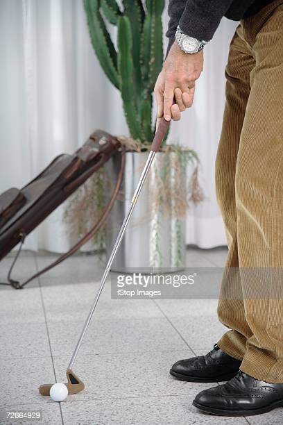 Man playing golf indoors on tiled floor