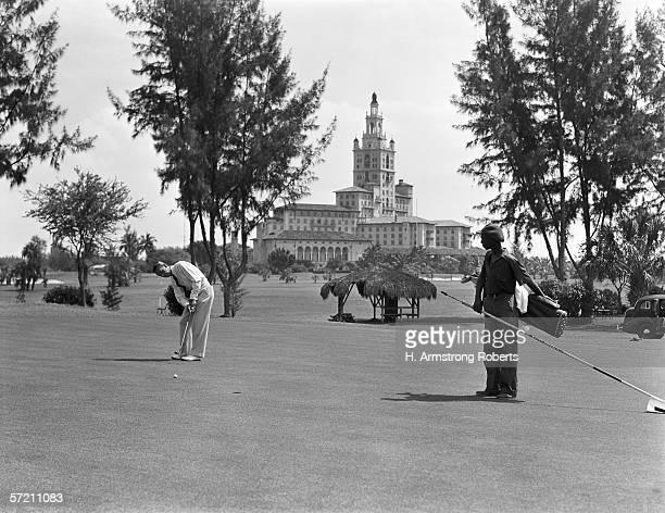 1930s: Man playing golf, Miami, Florida.