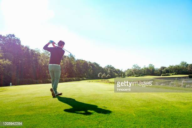 man playing golf on golf course - golf stock pictures, royalty-free photos & images