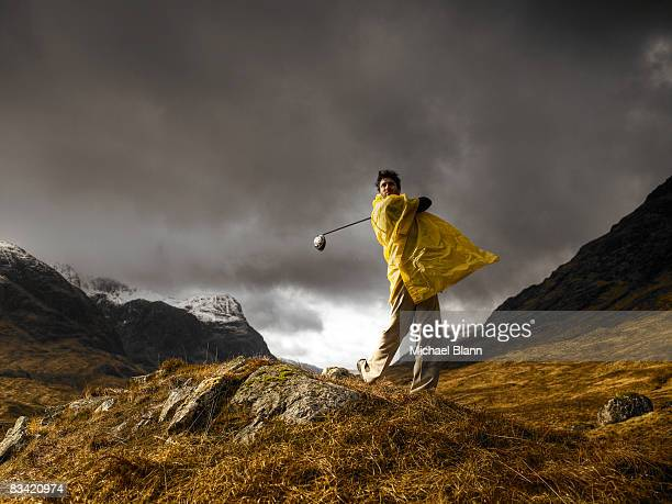 Man playing golf on mountain in rain
