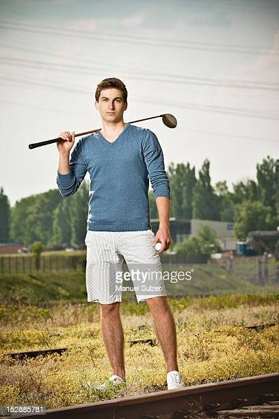Man playing golf on train tracks