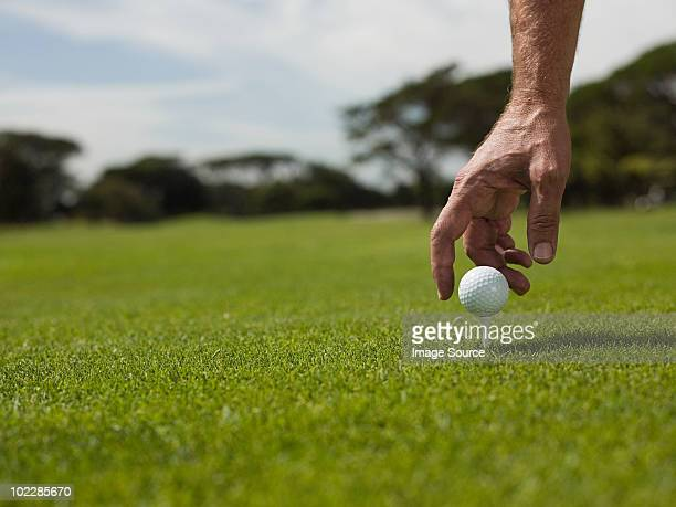 man playing golf, picking up ball - positioning stock pictures, royalty-free photos & images