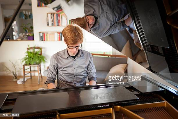 man playing grand piano - pianist front stock pictures, royalty-free photos & images