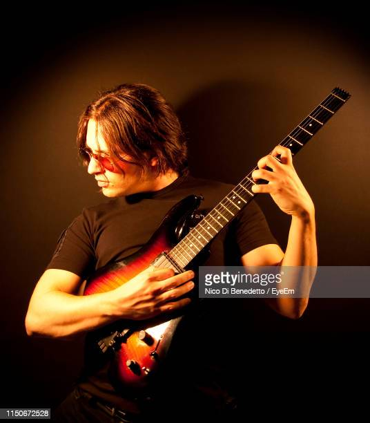 man playing guitar against black background - benedetto photos et images de collection