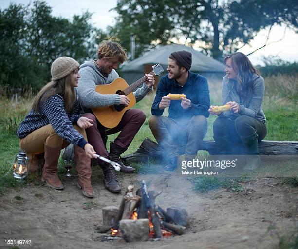 Man playing guitar around friends while glamping.