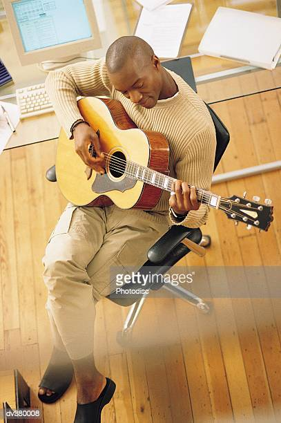 Man playing guitar at desk