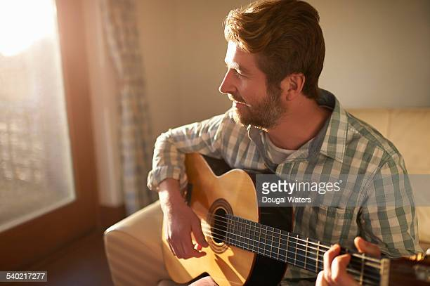 Man playing guitar at home.