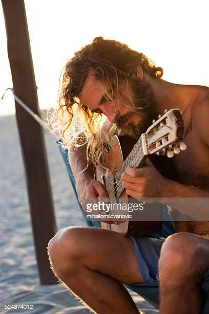 Man playing guitar at the beach