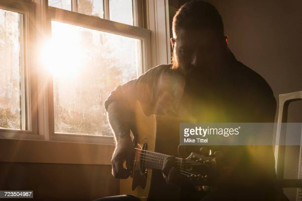 man playing guitar beside window - songwriter stock pictures, royalty-free photos & images