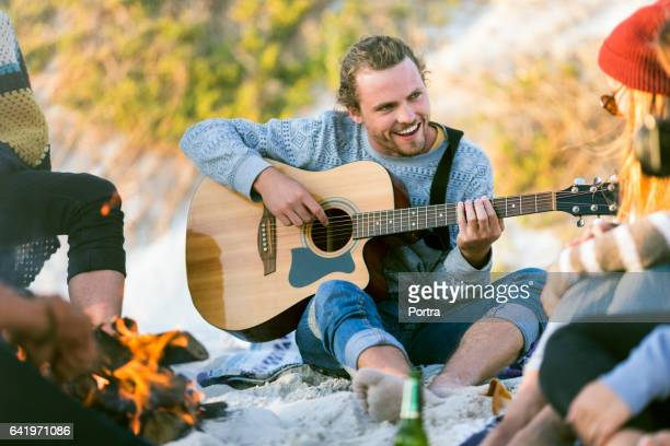 Man playing guitar for friends at beach