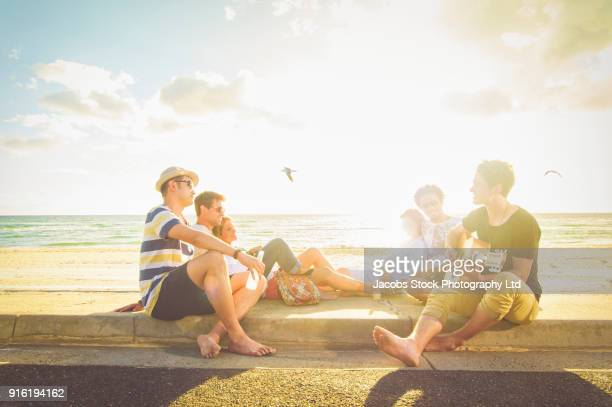 Man playing guitar for friends on beach