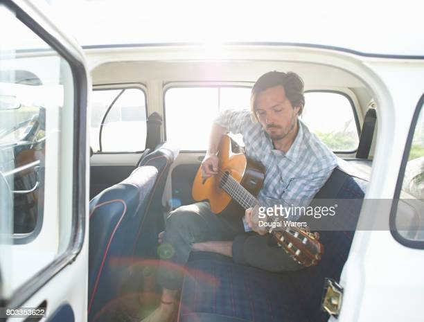man playing guitar in car back seat with door open. - acoustic guitar stock pictures, royalty-free photos & images