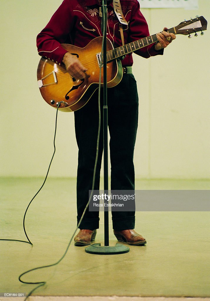 man playing guitar in front of mircrophone stand stock photo getty images. Black Bedroom Furniture Sets. Home Design Ideas