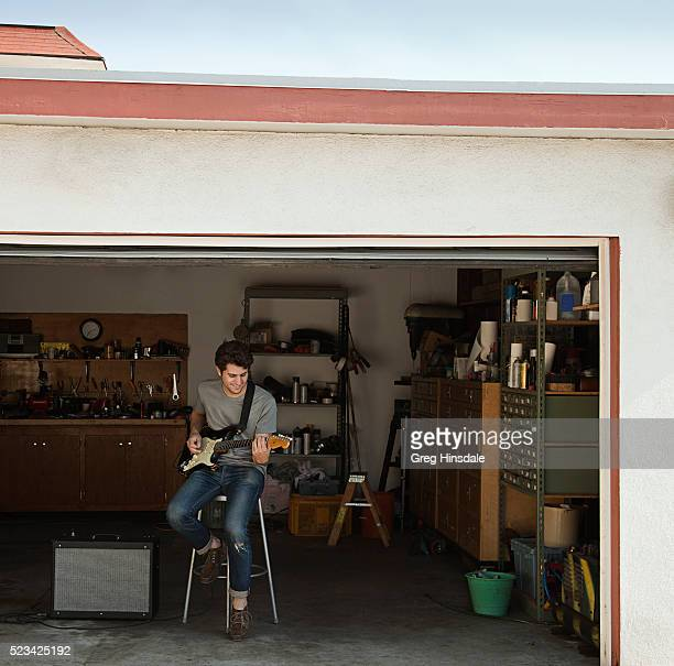 Man playing guitar in garage
