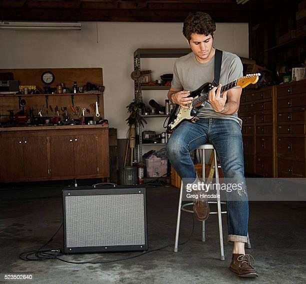 man playing guitar in garage - guitarrista fotografías e imágenes de stock