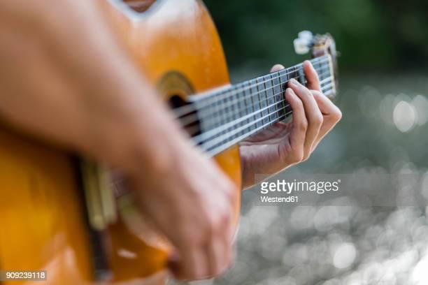 man playing guitar in nature, close-up - guitarra imagens e fotografias de stock