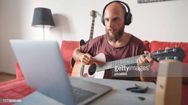 ラップトップでビデオチャットでギターを弾く男、バンドでオンラインでリハーサル - 爪弾く ストックフォトと画像