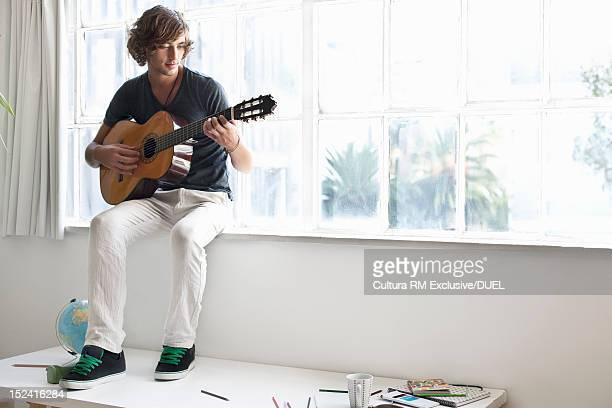 Man playing guitar in window