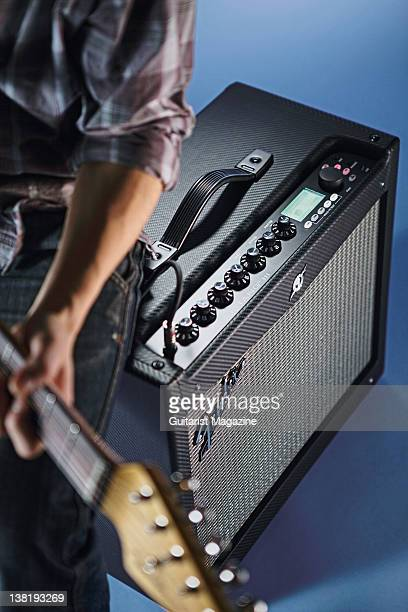 Man playing guitar next to a Fender Mustang III electric guitar amplifier. During a studio shoot for Guitarist Magazine/Future via Getty Images,...