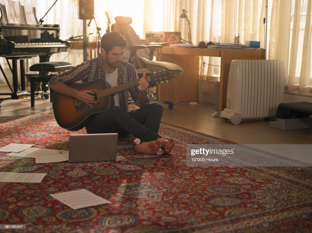 A man playing guitar next to a laptop : Stock Photo