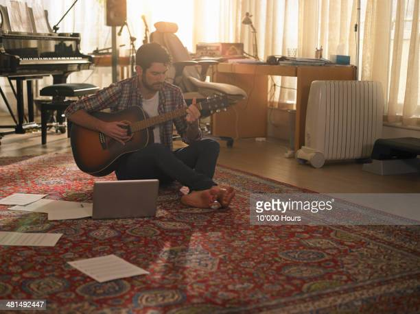 a man playing guitar next to a laptop - gitarre stock-fotos und bilder